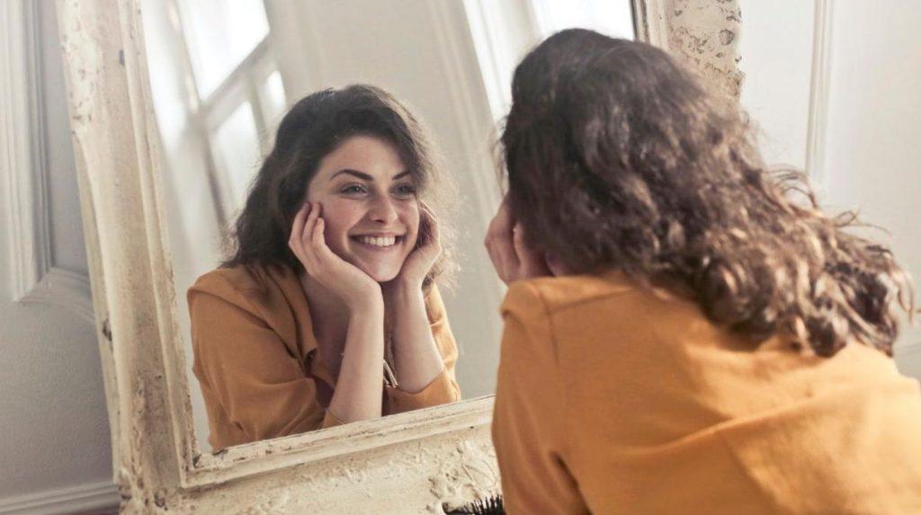 mujer mirandose al espejo sonriendo