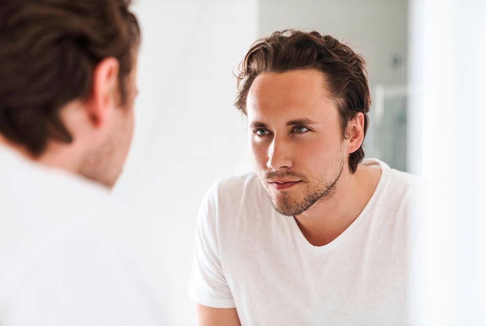 Hombre mirándose al espejo con una mirada firme