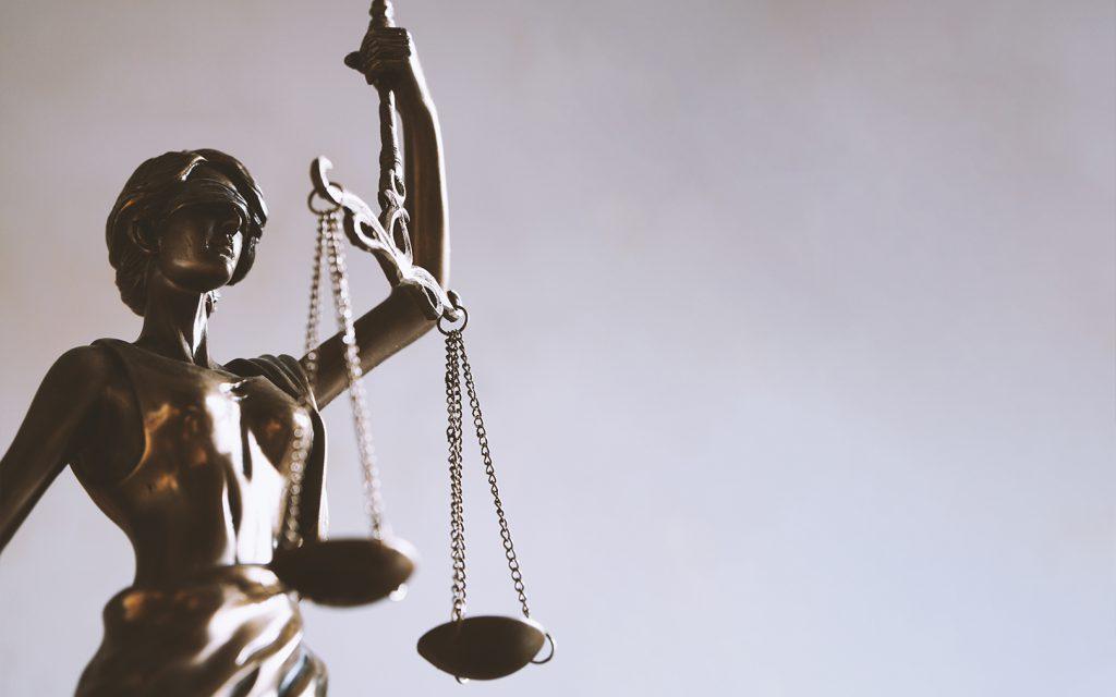 Podemos ver la imagen de la estatua de una mujer, con los ojos bendados sosteniendo una balanza. Así se representa a la Justicia, y es asociado con la abogacía
